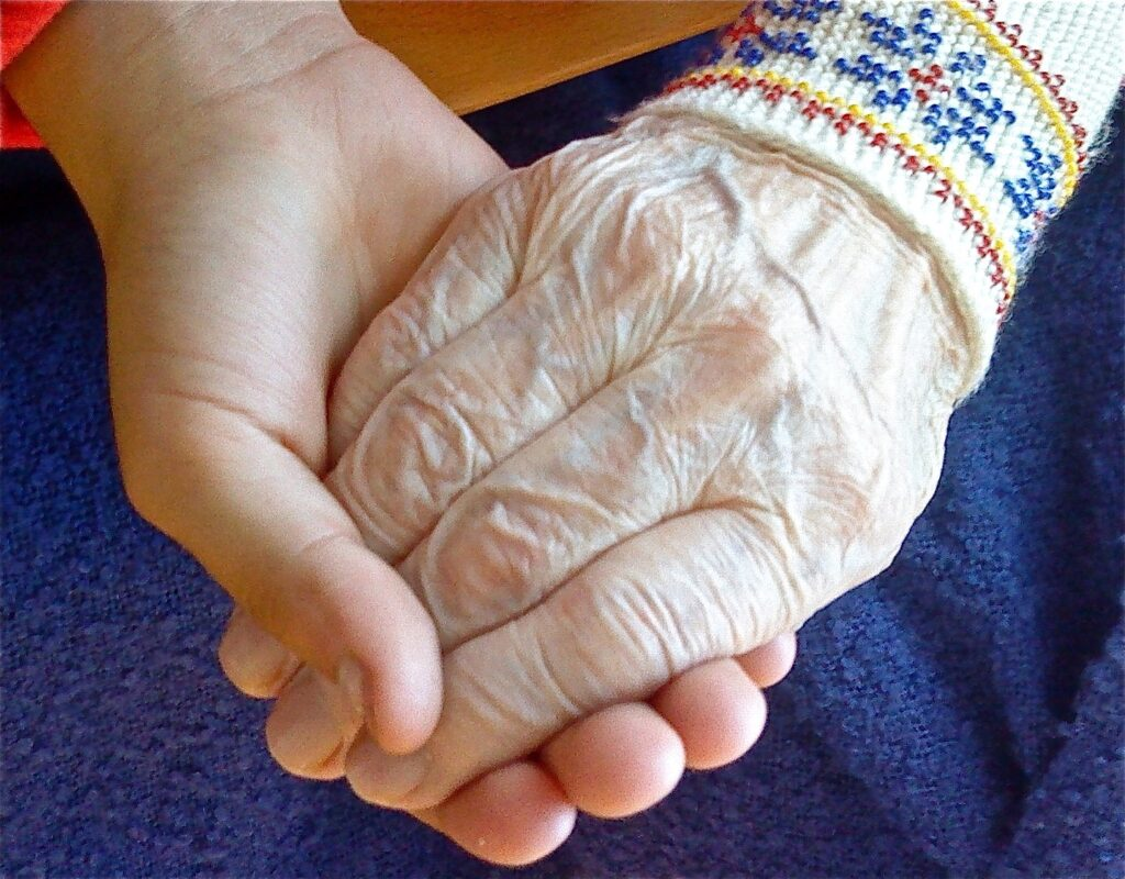 voksen og gammel hånd i hånd